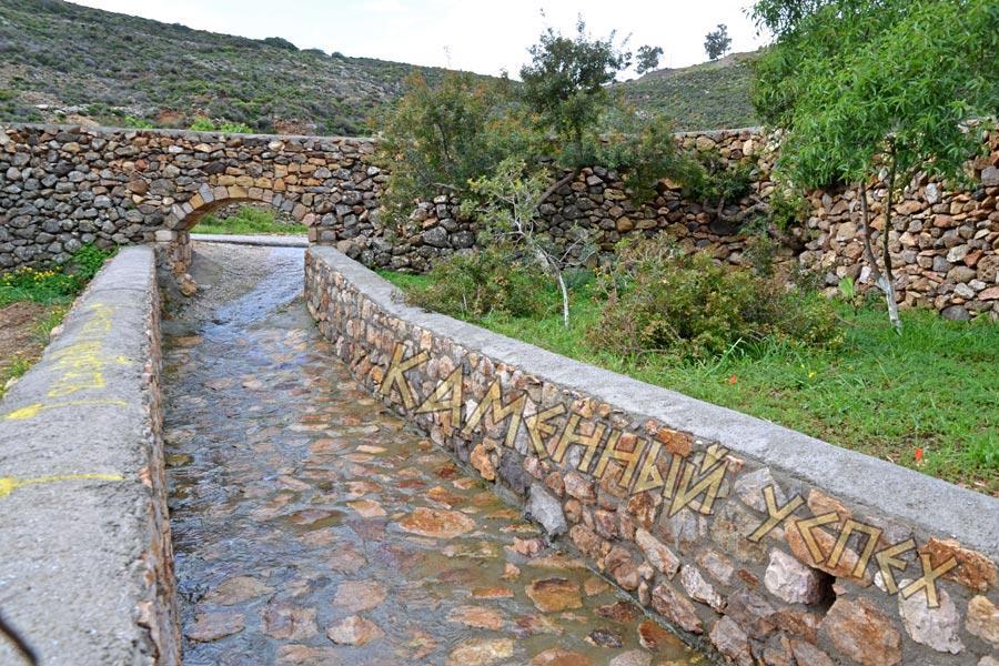 забор с аркой и речкой из камня